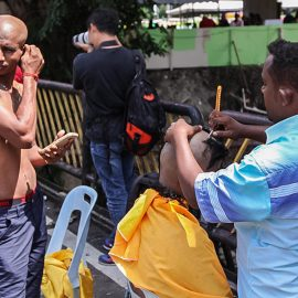 Photograph of a street barber shaving bald one of the Thaipusam pilgrims, photo by Ivan Kralj