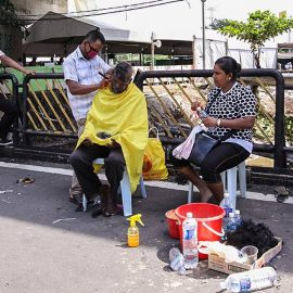 Photograph of a street barber shaving bald one of the Thaipusam pilgrims, while his wife obseres, photo by Ivan Kralj