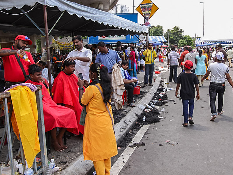 Photograph of street barbers shaving thhe heads of Thaipusam pilgrims, covering the streets in hair, photo by Ivan Kralj