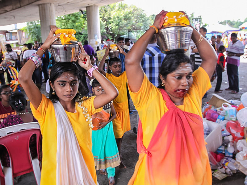 Photograph of a woman and her daughters carrying Paal Kudam milk pots on their heads, the woman's mouth are bleeding from the piercing ritual, photo by Ivan Kralj