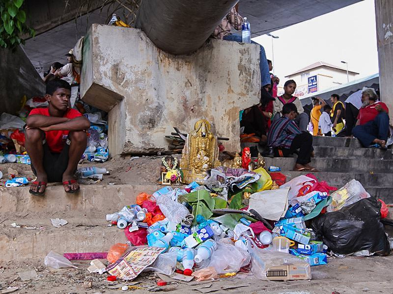 Photograph of a boy sitting next to a pile of garbage with some altar elements such as sculptures of deities, photo by Ivan Kralj