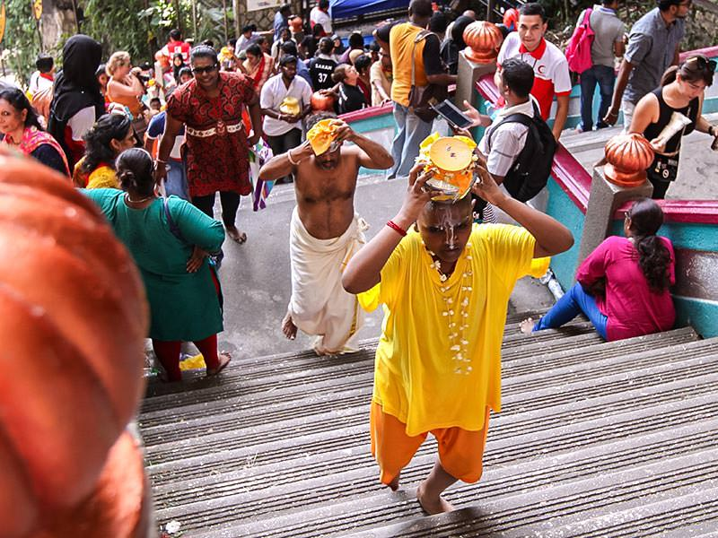 Photograph of pilgrims carrying Paal Kudam, brass pots filled with milk, as offerings for Thaipusam festival, the boy climbing the stairs to Batu Caves is spilling the milk all over his face, photo by Ivan Kralj