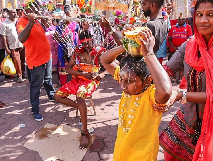 Photograph of a girl carrying a Paal Kudam, a pot of milk, spilling over her forehead, while her mother supports her at Thaipusam pilgrimage. At the background of the photo, a young guy is resting on chair while carrying a Kavadi, a heavy portable altar with skewers attached to his torso, photo by Ivan Kralj
