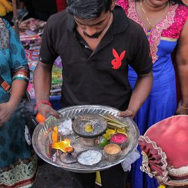 A man in a black T-shirt, with the red logo of Playboy magazine, holding a plate with sacred ashes ath Thaipusam festival, photo by Ivan Kralj