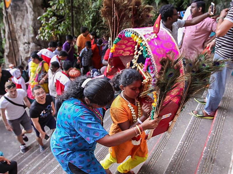 Photograph of a mother helping her young daughter carrying a heavy Kavadi altar while climbing the stairs of Batu Caves for Thaipusam festival, photo by Ivan Kralj