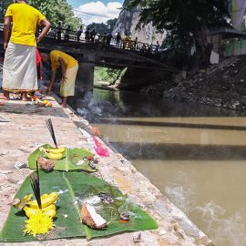 Photograph of offerings left at the river at Thaipusam - on the base of the banana leave there is a part of the coconut shell, bananas, flowers and incenses, photo by Ivan Kralj