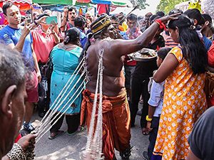 Photo of a man with his back pierced with hooks which are attached to the chains pulled by another man, resembling a horse pulling the carriage - the man is giving blessings to other pilgrims at Thaipusam 2017, photo by Ivan Kralj