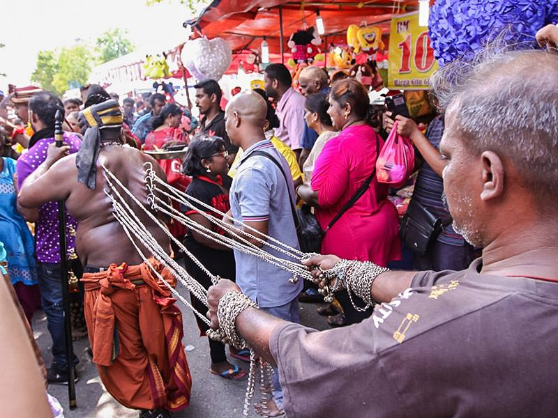 Photograph of a man pulling the chains attached to the hooks piercing the skin of the back of the other man, an extreme ritual at Thaipusam festival, photo by Ivan Kralj