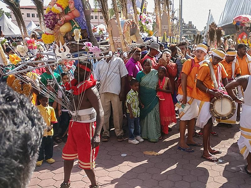 Photograph of a Thaipusam pilgrim dancing while carrying a Kavadi, a portable altar at Thaipusam, while the crowds observe - the structure is worn on his shoulders while the skewers are pressing the bearer's torso, photo by Ivan Kralj