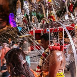 Photograph of a Thaipusam pilgrim carrying a Kavadi, a portable altar at Thaipusam - the structure is worn on his shoulders while the skewers are pressing the bearer's torso. Pilgrim is entering Batu Caves, photo by Ivan Kralj