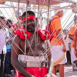 Photograph of a Thaipusam pilgrim resting while wearing a Kavadi, a portable altar at Thaipusam - the structure is worn on his shoulders while the skewers are pressing the bearer's torso, photo by Ivan Kralj