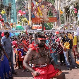 Photograph of a Thaipusam pilgrim resting while carrying a Kavadi, a portable altar at Thaipusam - the structure is worn on his shoulders while the skewers are pressing the bearer's torso, photo by Ivan Kralj