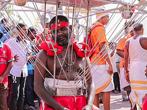 Photograph of a pilgrim sitting and resting while wearing a Kavadi, a portable altar with skewers piercing the skin of his torso at Thaipusam festival, photo by Ivan Kralj