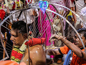 Photograph of a man who carried the kavadi up the hill having its skewers removed in Batu Caves at Thaipusam festival, photo by Ivan Kralj