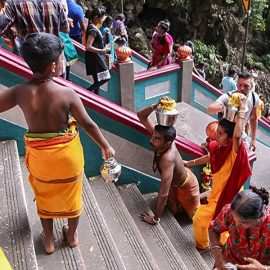 Photograph of a boy at the stairs of Batu Caves, providing space for his father's climb - his father is carrying Paal Kudam, brass pot filled with milk, on his head, while moving on his knees at Thaipusam festival, photo by Ivan Kralj