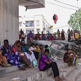 Photograph of Thaipusam pilgrims resting in the shade at the river bank at Thaipusam festival