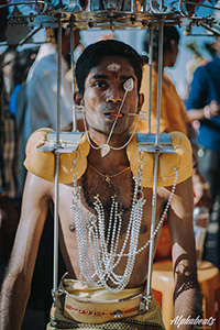 Photo of Prakash J Govindarajoo, a pilgrim at Thaipusam 2017, with his mouth and tongue pierced, carrying a kavadi, photo by Alphabeatz Production