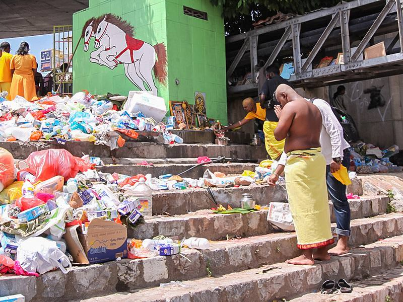 Photograph of a pilgrim praying in front of the improvised altars in piles of trash at the river bank at Thaipusam festival