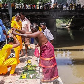 Photograph of the family father putting the Paal Kudam at his family member's head after the ritual at the river at Thaipusam, photo by Ivan Kralj