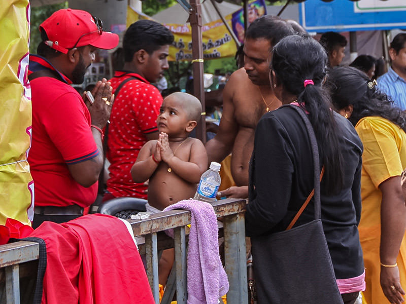 Photograph of a toddler giving a gesture of thanks to the street barber that shaved him bald at Thaipusam, photo by Ivan Kralj