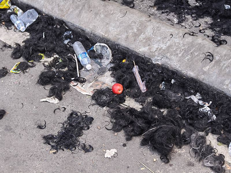 Photograph of a street covered with hair and some garbage, left after the barbers shaved thousands of Thaipusam pilgrims, photo by Ivan Kralj