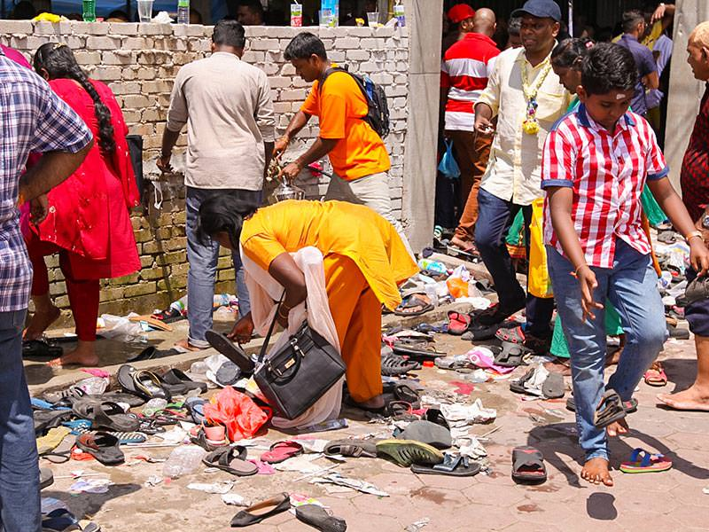Photograph of a woman searching for her shoes at the entrance of one of the temples at Batu Caves - with million and half of visitors at Thaipusam shoes get easily lost, photo by Ivan Kralj