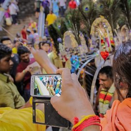 Photograph of tourists photographing the Kavadi bearer removing his skewers and piercings, photo by Ivan Kralj