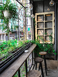 Balcony at The Laban hotel in Saigon, with green plants, light bulbs and rustical wooden details