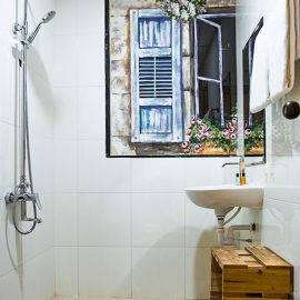 Photo of the bathroom in The Laban hotel, with shower, sink, wooden box, painting of the window on the wall, photo by Ivan Kralj
