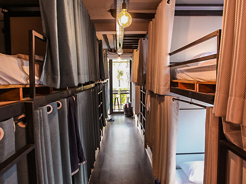 Photo of a dormitory in The Laban hotel, two rows of curtained bunk beds separated by the corridor between them, big lightbulbs, photo by Ivan Kralj