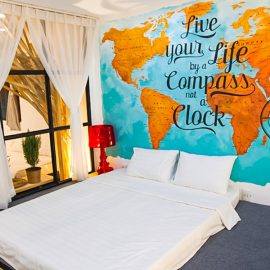 "The photo of a bed in the room of The Laban hotel, with ""Live your Life by a Compass, not a Clock"" message on the wall"
