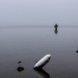 A fisherman standing knee-deep in the snow-surrounded Chuzenji Lake, close to Nikko, Japan, photo by Ivan Kralj