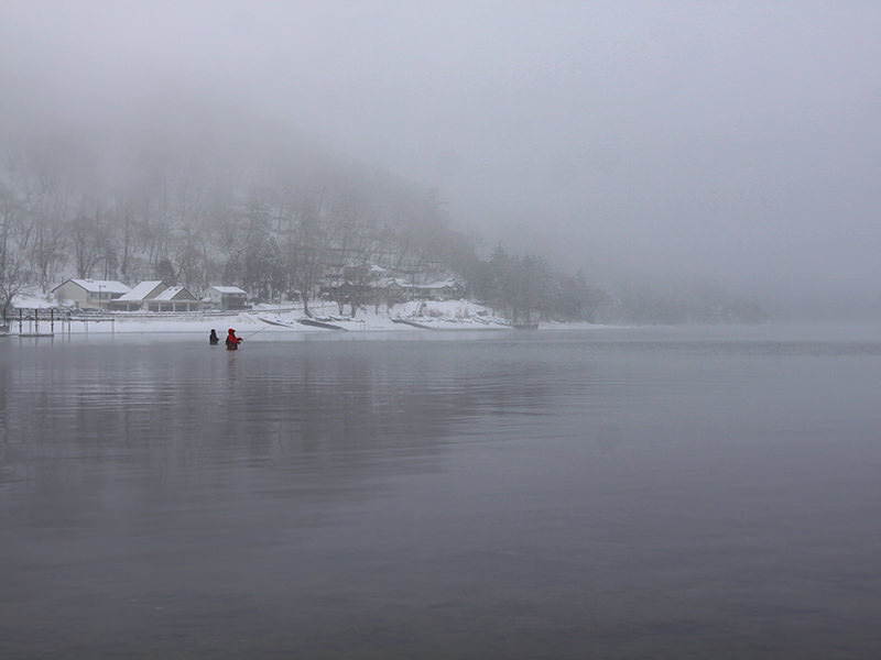 Two fishermen standing waist-deep in the snow-surrounded Chuzenji Lake, close to Nikko, Japan, photo by Ivan Kralj