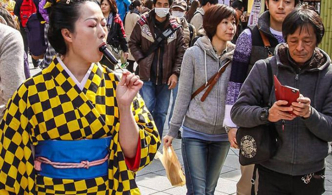 The lady in eccentric yellow-black checkered kimono is licking a penis-shaped lollipop in the street at Kanamara Matsuru, festival of the iron penis, in Kawasaki, Japan, photo by Ivan Kralj