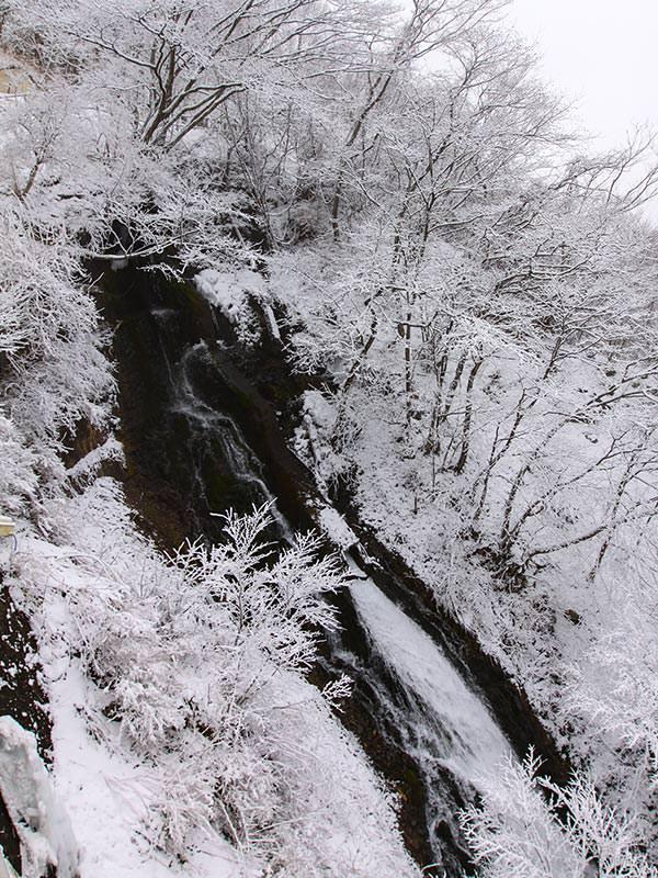 Kegon Falls' water making its way through the snowy surrounding, birds eye perspective, Japan, photo by Ivan Kralj