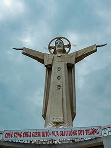 The monumental statue of Christ the King in Vung Tau, Vietnam, stretching his arms in front of the dark clouds, photo by Ivan Kralj