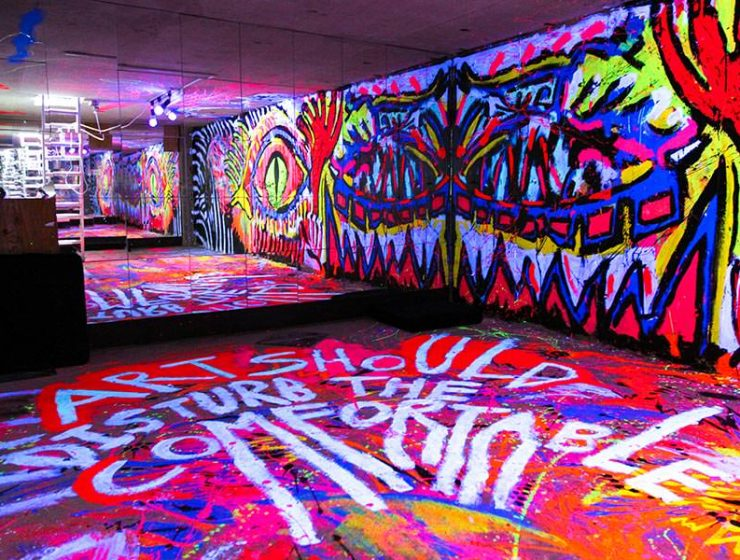 "One of the most colorful rooms in hostels in Tokyo, Japan: basement in ARTnSHELTER hostel with walls painted in fluorescent colors, and ""Art should disturb the comfortable"" message on the floor, by Singaporean street artist Zon, photo by Ivan Kralj"
