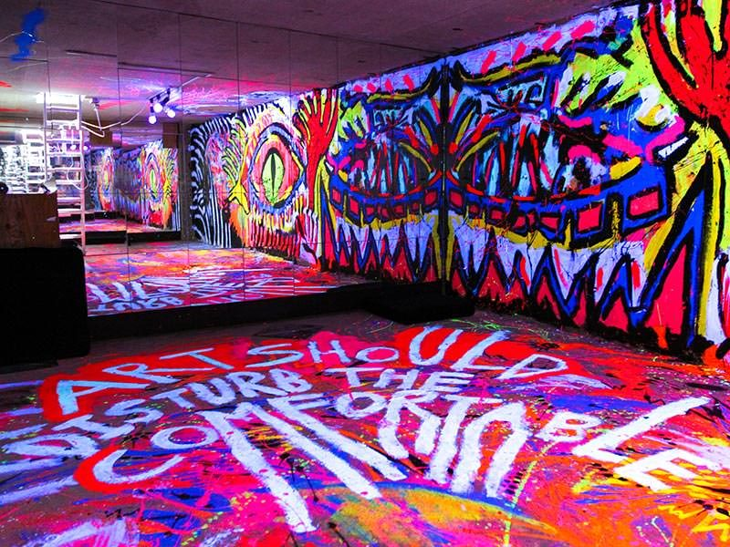 """One of the most colorful rooms in hostels in Tokyo, Japan: basement in ARTnSHELTER hostel with walls painted in fluorescent colors, and """"Art should disturb the comfortable"""" message on the floor, by Singaporean street artist Zon, photo by Ivan Kralj"""