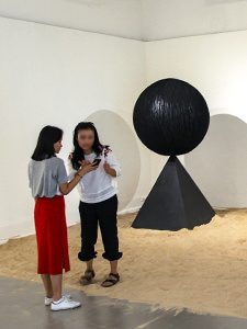 "The girl checking how did she turn out on the photograph for which she was posing in the middle of Monica Hapsari's artwork ""Antara"", sitting in the sand as if on a beach, at Galeri Nasional Indonesia, Jakarta, EXI(S)T - Tomorrow As We Know It exhibition, photo by Ivan Kralj"