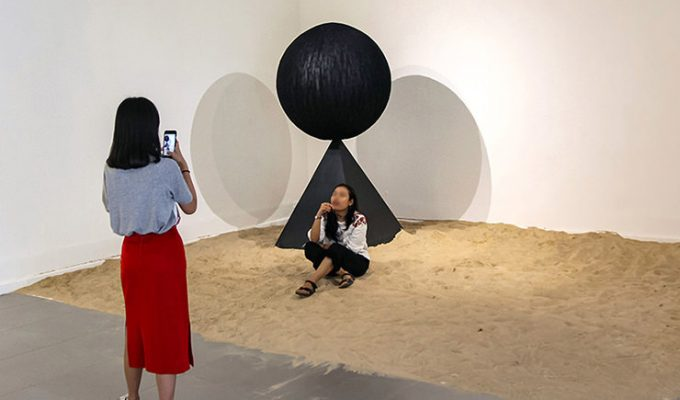"Art of making selfies: The girl posing for a photograph in the middle of Monica Hapsari's artwork ""Antara"", sitting in the sand as if on a beach, at Galeri Nasional Indonesia, Jakarta, EXI(S)T - Tomorrow As We Know It exhibition, photo by Ivan Kralj"