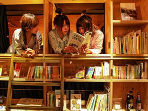 Not many hostels in Tokyo provide pyjamas for guests: Japanese girls dressed for sleeping, reading books in the bookshelf dormitory in Book and Bed hostel in Tokyo, Japan, photo by Ivan Kralj