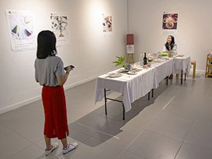 "Art of making selfies: The girl posing for a photograph at the table of Hapsari's artwork ""Antara"", sitting in the sand as if on a beach, at Galeri Nasional Indonesia, EXI(S)T - Tomorrow As We Know It exhibition, photo by Ivan Kralj"
