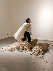 "Art of making selfies: The girl visitor of Galeri National Indonesia in Jakarta, running over the jute sacks, while carrying the dress on a hanger in hands, all elements of Ratu R. Saraswati's artwork ""I Beg I Promise"". This shocking intervention in the art installation is explained by the girl's intention to be photographed for social media, at the EXI(S)T - Tomorrow As We Know It exhibition, photo by Ivan Kralj"