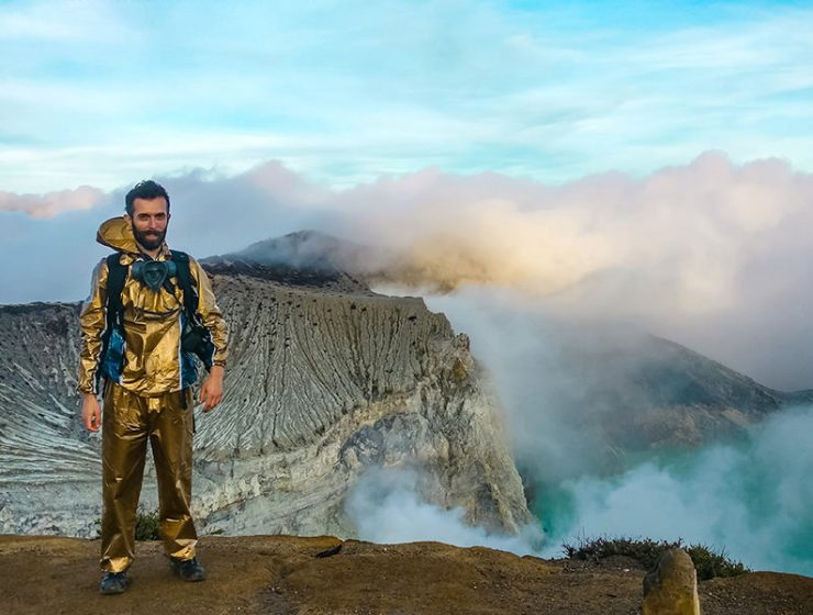 Pipeaway blogger Ivan Kralj dressed in golden gear standing on the edge of the Ijen Volcano in East Java, clouds, mountain and blue crater lake visible in the background