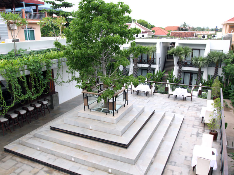 Jaya House River Park hotel terrace, with a tree protruding the roof from the restaurant below, in Siem Reap, Cambodia, photo by Ivan Kralj