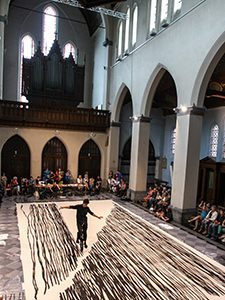 "Unicycle rider Kenzo Tokuoka performs his ""Sho-Ichido"" performance in a church in Ghent, Belgium - his unicycle tyre dipped in black paint leaves traces on the large piece of canvas, at Miramiro festival, photo by Ivan Kralj"