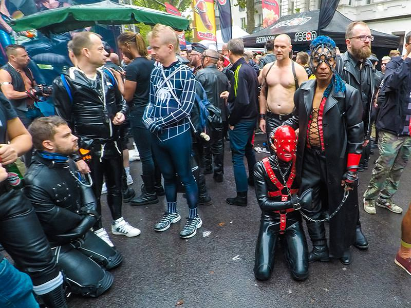 Leather man with a mask-covered slave on a leash at Folsom Europe Street Fair, the biggest European gay fetish event, in Berlin, Germany, photo by Ivan Kralj
