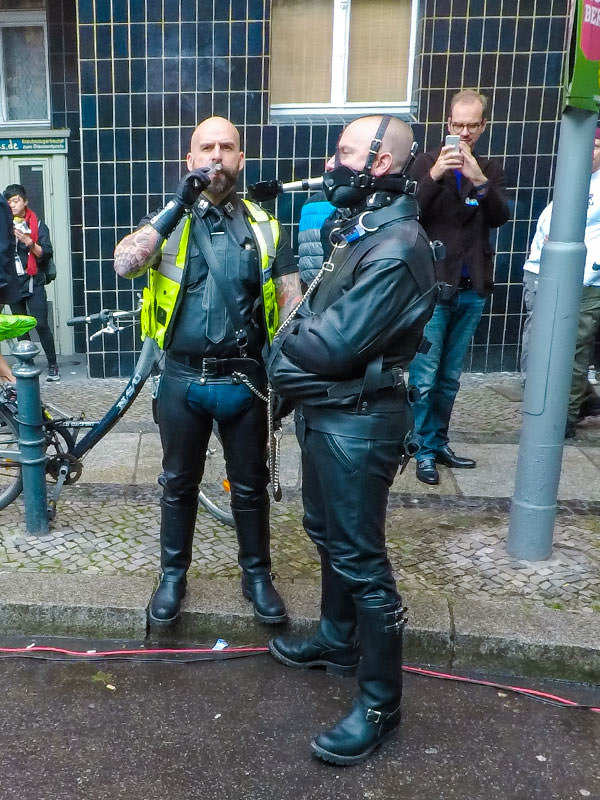 A man smoking a cigar and the slave holding an ashtray with his mouth at Folsom Europe Street Fair, the biggest European gay fetish event, in Berlin, Germany, photo by Ivan Kralj