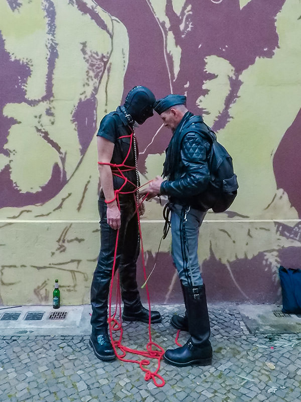 Master is tying his mask-covered slave with shibari style ropes at Folsom Europe Street Fair, the biggest European gay fetish event, in Berlin, Germany, photo by Ivan Kralj