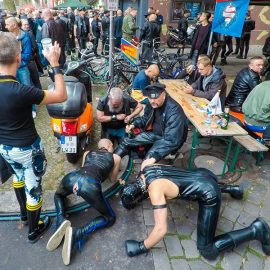 Two slaves are licking the boots of their master while he is enjoying his beer at Folsom Europe Street Fair, the biggest European gay fetish event, in Berlin, Germany, photo by Ivan Kralj